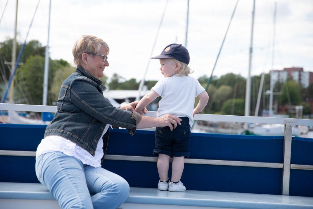 Aikuinen ja lapsi aluksen aurinkokannella purjeveneiden edustalla