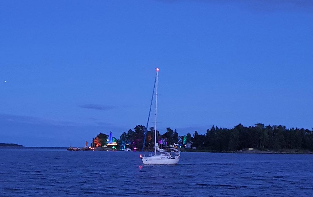 Purjevene yöllä merellä, taustalla värikkäitä valoja