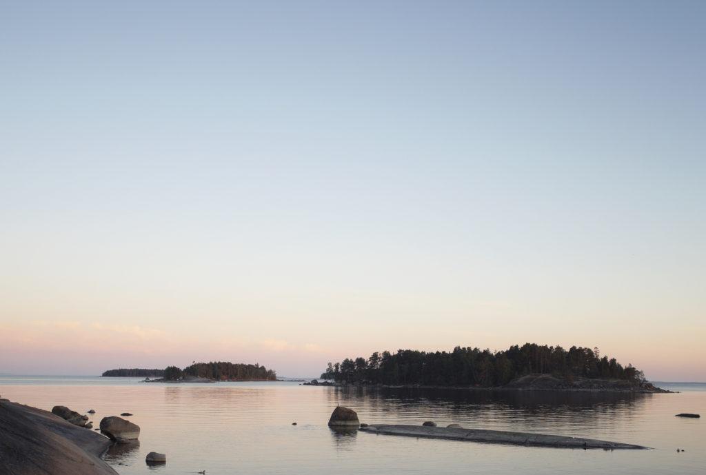 Kaksi saarta ja edustalla kalliota myöhäisessä kesäillassa.
