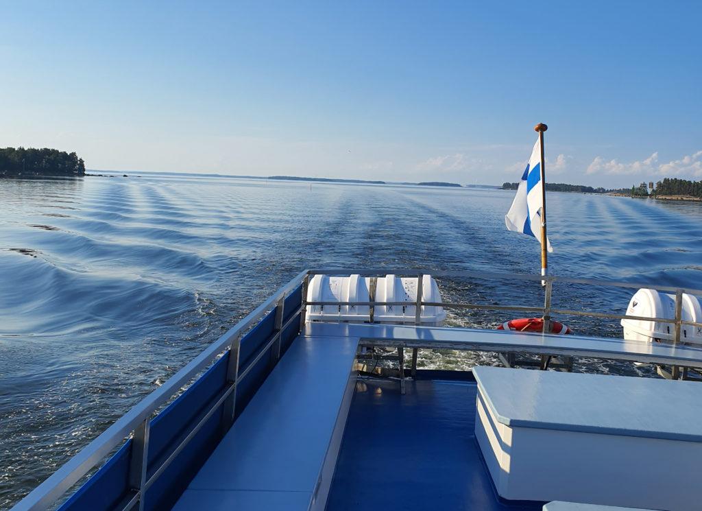 Aluksen perästä aurinkokannelta kuvattu aava merimaisema ja Suomen lippu.