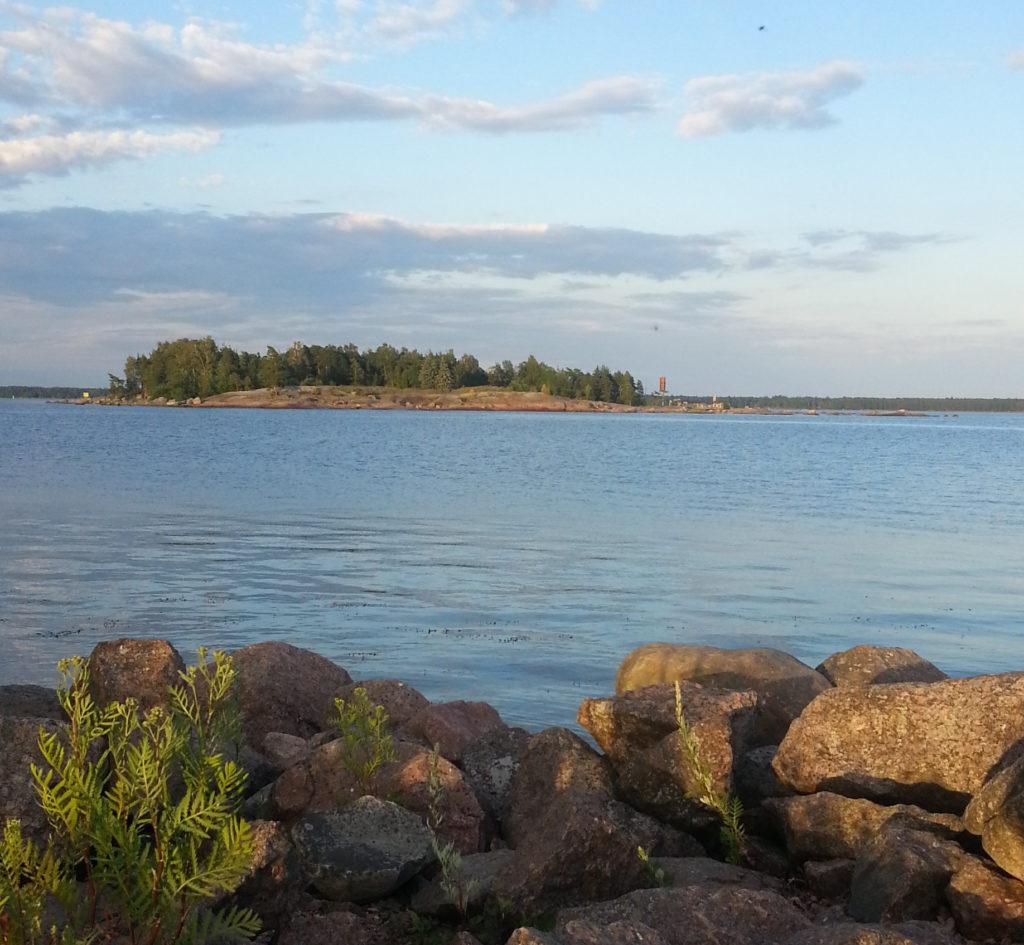 Merimaisemaa illansuussa. Taustalla on saari ja edustalla kivikkoa alkavassa ilta-auringossa.