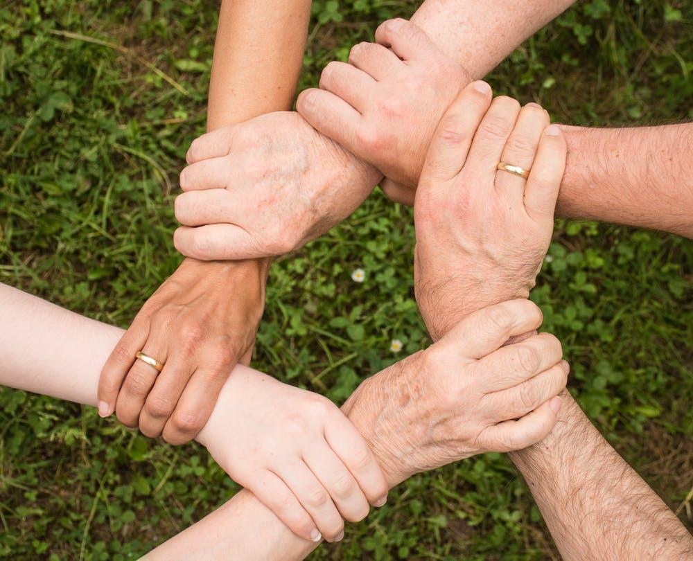 Kuusi henkilöä pitelee toisiaan ranteista tähtimäisessä muodostelmassa