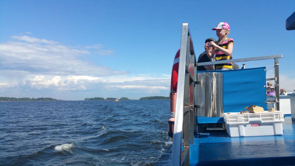 Lettipäinen tyttö lippalakki päässä kuvaa kameralla merimaisemaa aluksen aurinkokannelta.